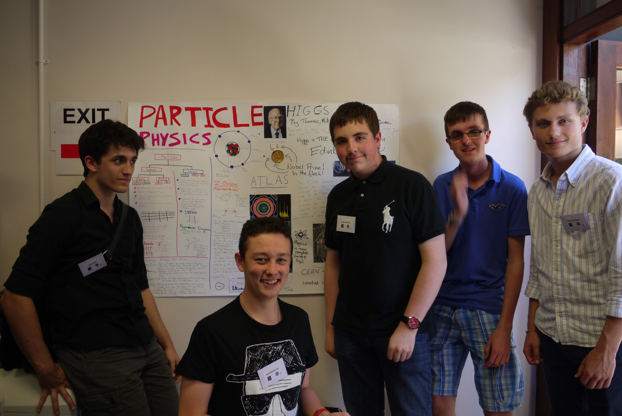 The particle physics team in front of their poster.