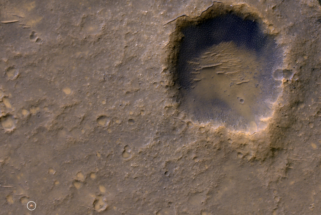 Near the lower left corner of this view is the three-petal lander platform that NASA's Mars Exploration Rover Spirit drove off in January 2004. The lander is still bright, but with a reddish color, probably due to accumulation of Martian dust. The High Resolution Imaging Science Experiment (HiRISE) camera on NASA's Mars Reconnaissance Orbiter recorded this view on Jan. 29, 2012, providing the first image from orbit to show Spirit's lander platform in color. The view
