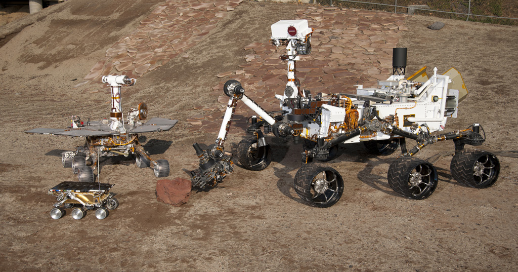 The setting is JPL's Mars Yard testing area. Front and centre: flight spare for the first Mars rover, Sojourner, which landed on Mars in 1997 as part of the Mars Pathfinder Project. Left: a Mars Exploration Rover Project test rover that is a working sibling to Spirit and Opportunity, which landed on Mars in 2004. Right: a Mars Science Laboratory test rover the size of that project's Mars rover, Curiosity,