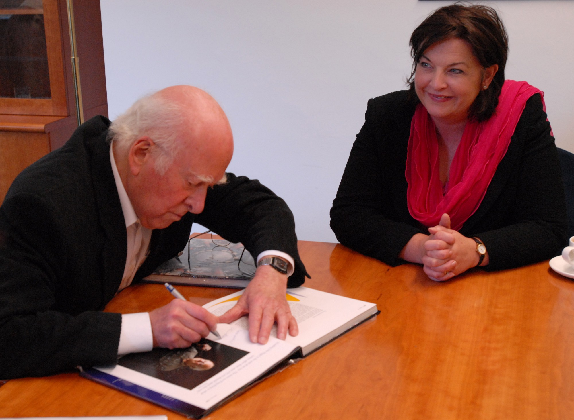 Peter Higgs autographing the ATLAS book 'Exploring the Mystery of Matter' presented to Fiona Hyslop, on the right.