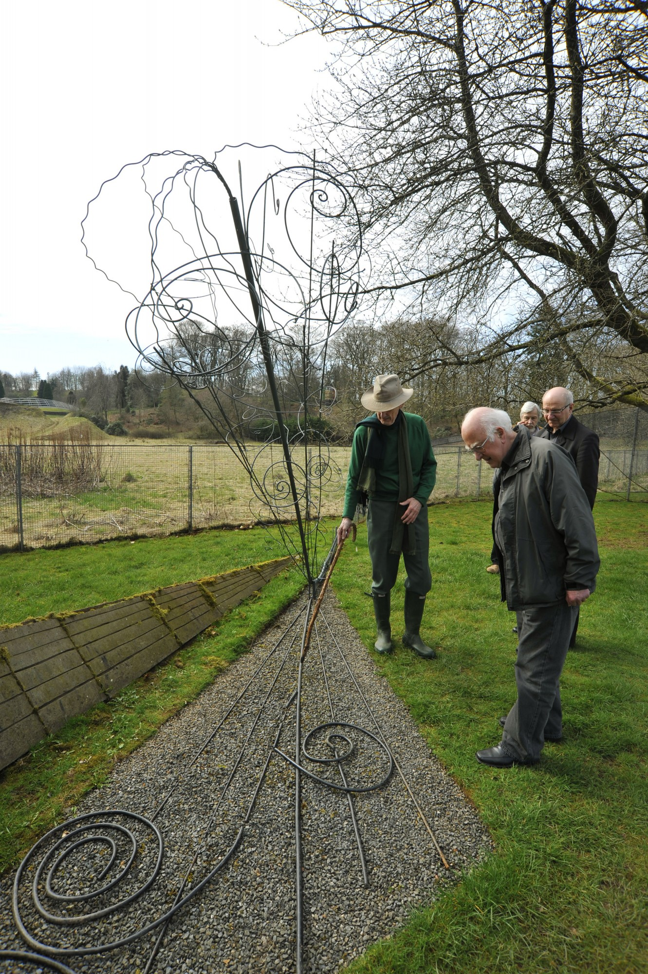Peter Higgs and Charles Jencks admiring the bubble chamber tracks sculpture. In the background are Alan Walker and Rolf Heuer