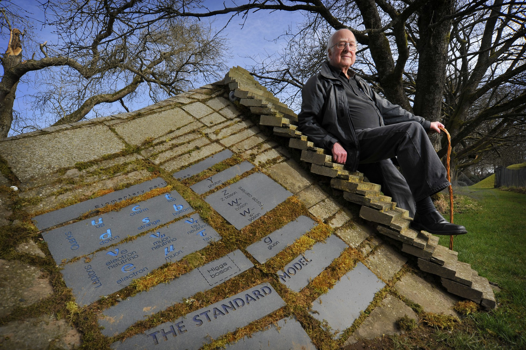Peter Higgs resting against the Standard Model landscape sculpture that includes the Higgs Boson.