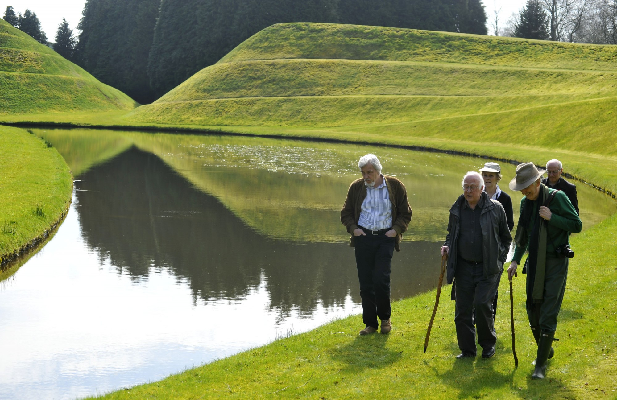 Left to right: Rolf Heuer, Peter Higgs and Charles Jencks walk alongside one of the garden's artificial lakes. Behind are James Gillies and Alan Walker. In the background on the left is the 'double helix' mound.