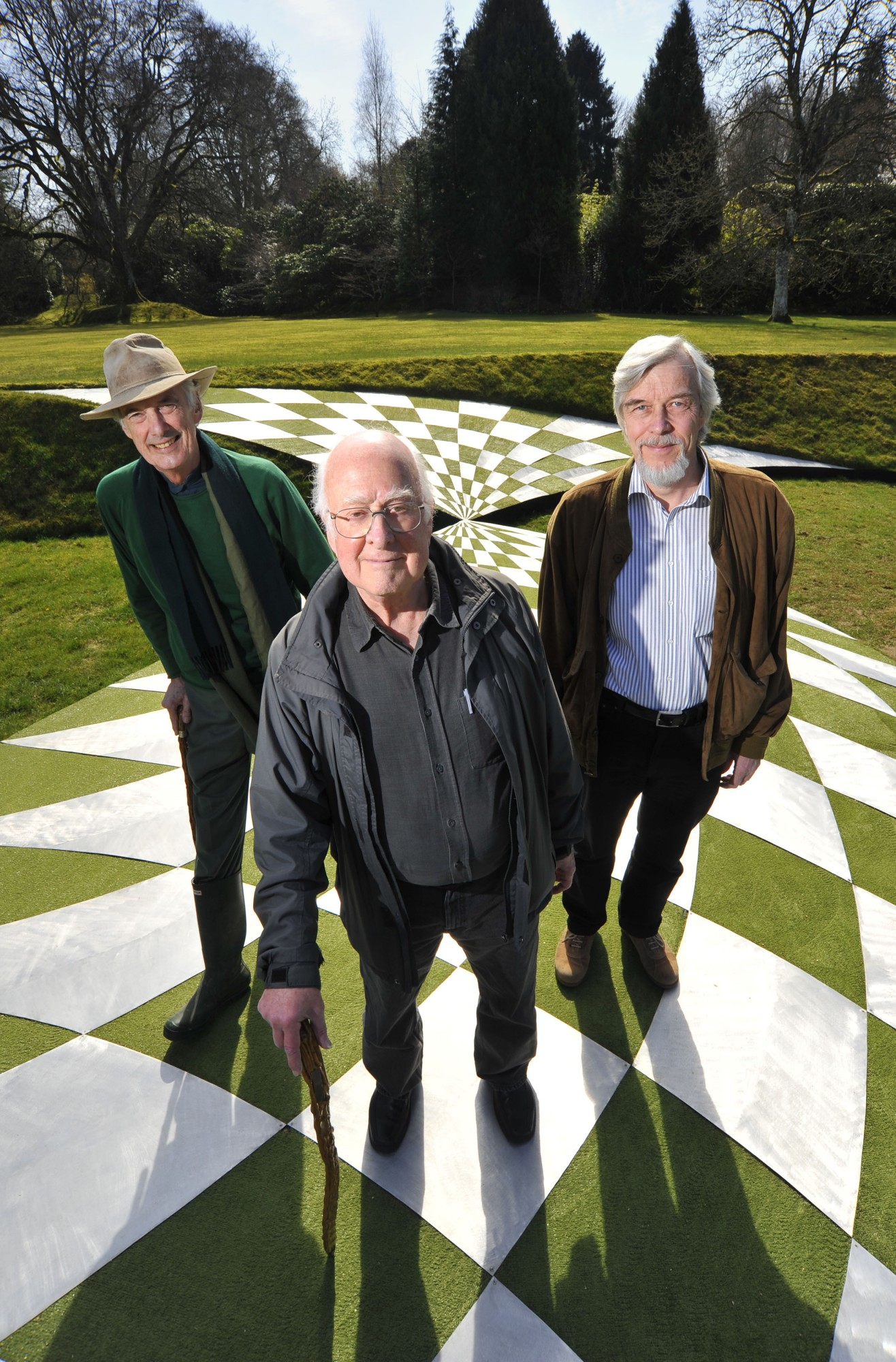 Left to right: Charles Jencks, Peter Higgs and Rolf Heuer standing on Charles' representation of space-time in the vicinity of a black hole