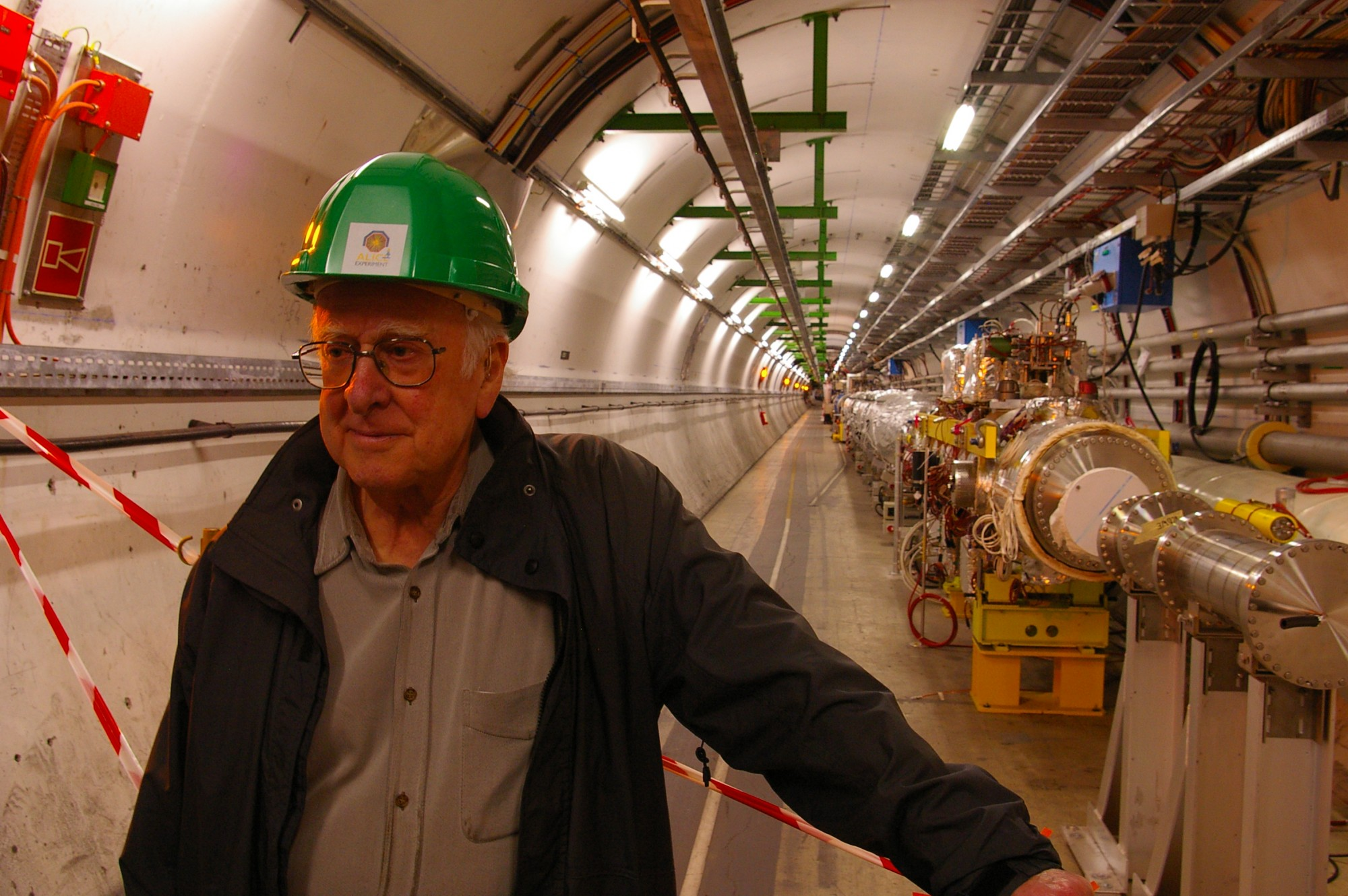 Peter Higgs in the long straight section of the Large Hadron Collider tunnel, just before the underground ALICE experimental hall. Photograph copyright Alan Walker, University of Edinburgh.