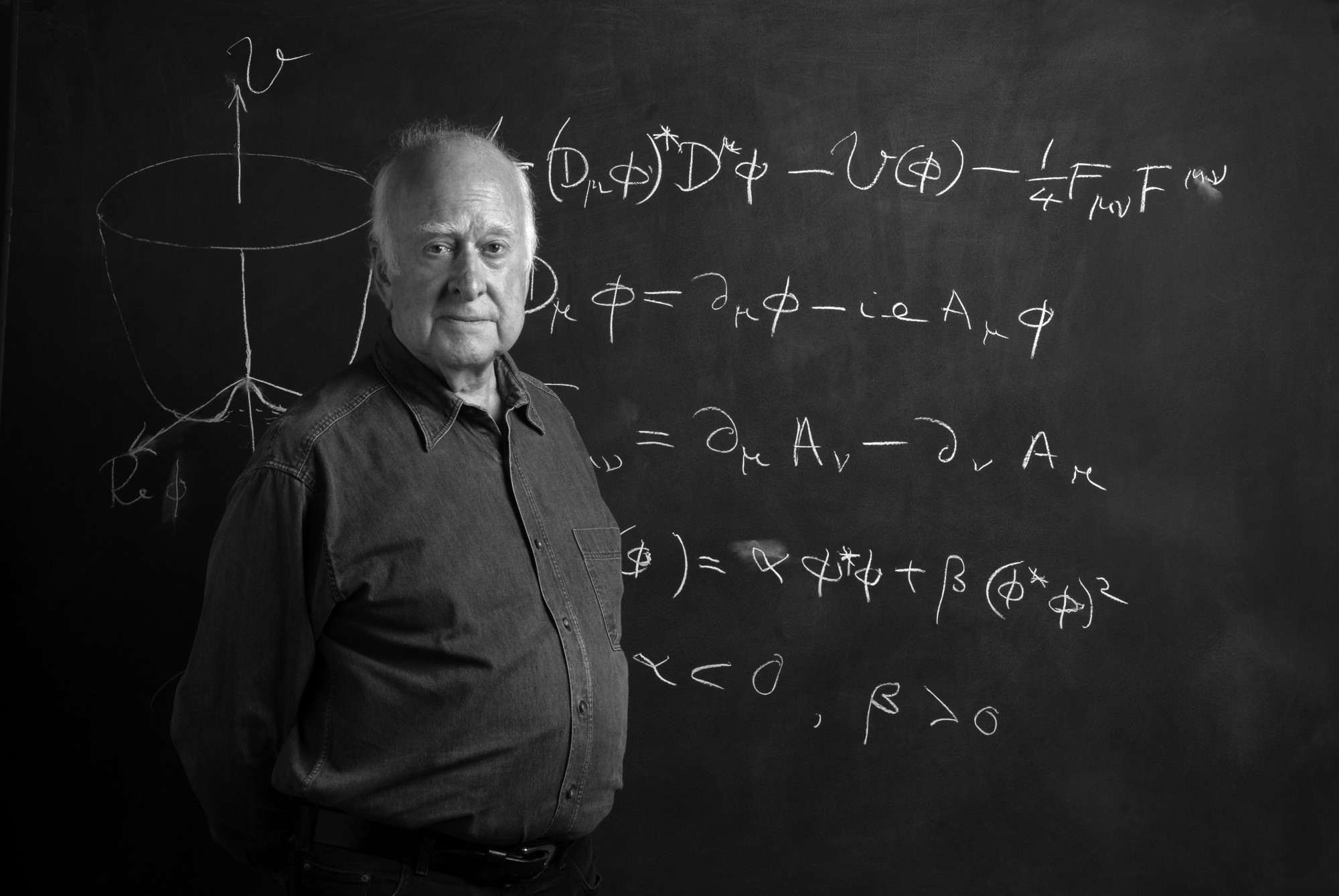 B&W photographic portrait of Peter Higgs, in front of blackboard, taken by Peter Tuffy. 17 June 2009.