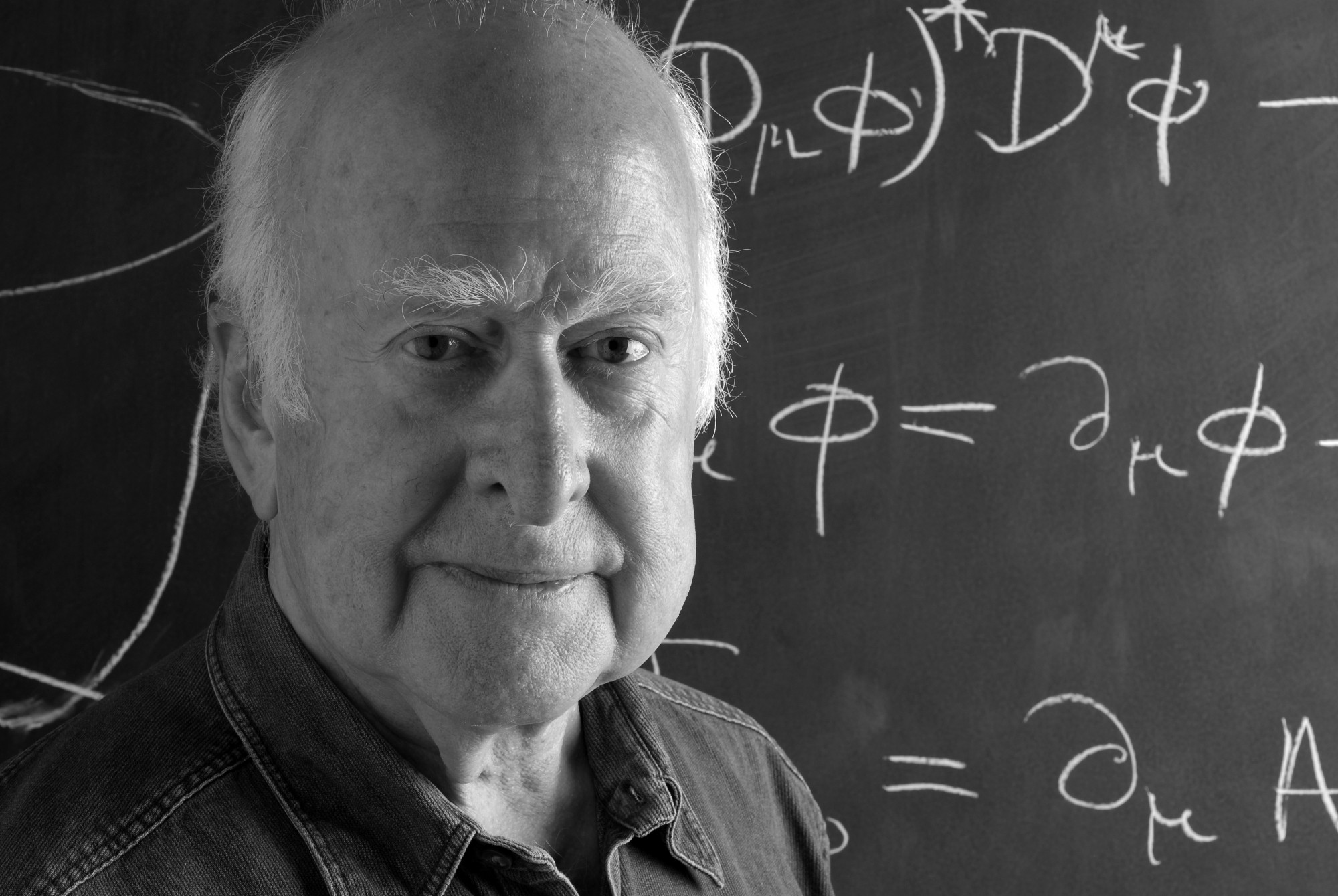 B&W close-up photographic portrait of Peter Higgs, in front of blackboard, taken by Peter Tuffy. 17 June 2009.